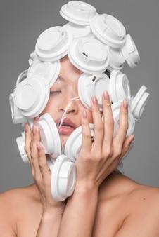 Face frontal da mulher asiática sendo coberto por tampas de plástico branco