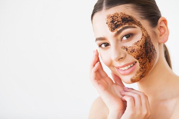 Face skin scrub. menina sorridente, aplicação de máscara de café esfoliante na pele.