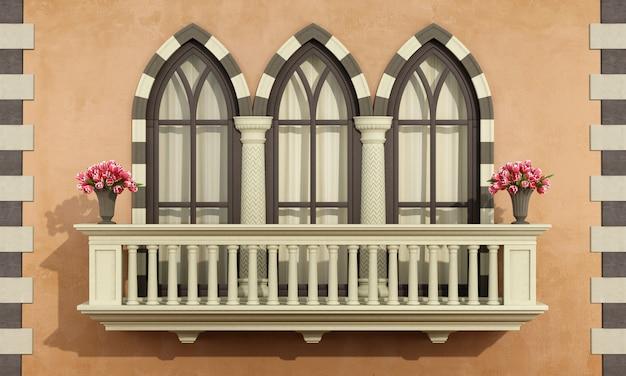 Fachada antiga com balaustrada de varanda clássica e três janelas góticas