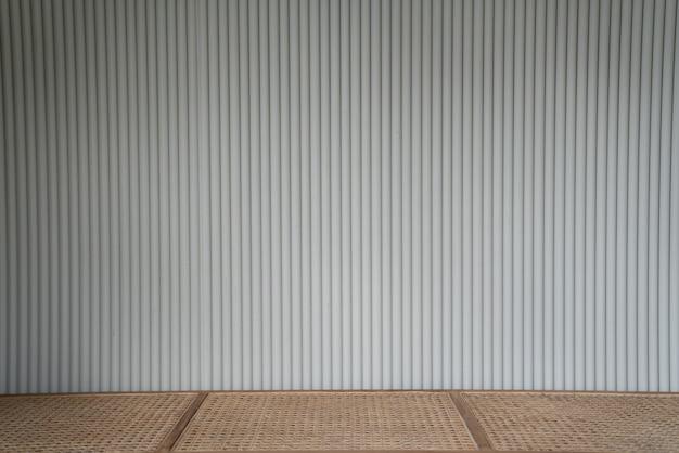 Fachada de chapa de madeira corrugada na cor branca com banco de vime superior vazio