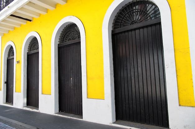 Fachada de construção amarela com portas de madeira marrom e arco ao ar livre