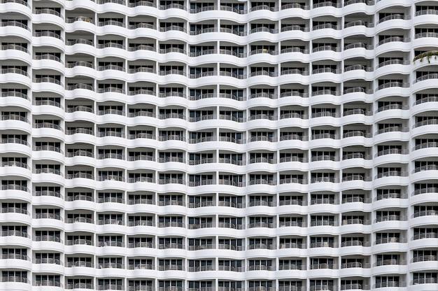 Fachada de edifício sem emenda, filas de hotel muitos varanda com forma curvada