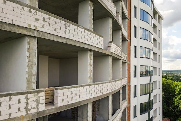 Fachada de prédio de apartamentos novo com muitas janelas e cômodos planos em construção.