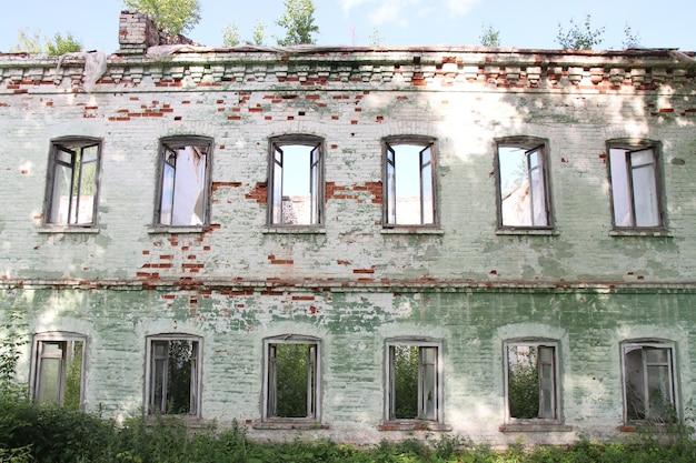 Fachada de um antigo prédio de tijolos em ruínas com janelas que abrem