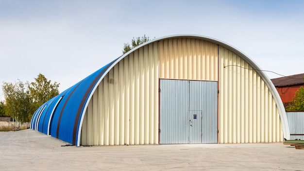 Fachada de um armazém de metal azul, edifício comercial para armazenamento de mercadorias.