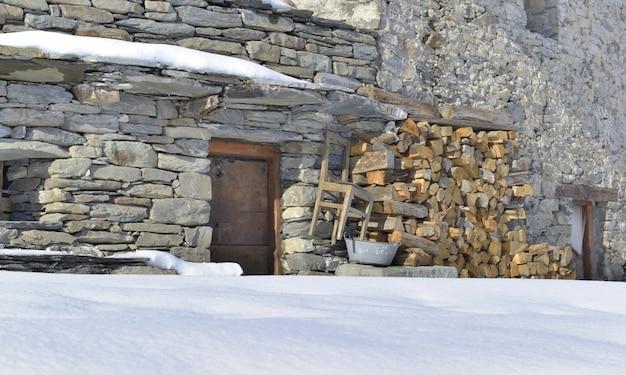 Fachada de uma casa alpina tradicional chapada com firrewood empilhada no inverno