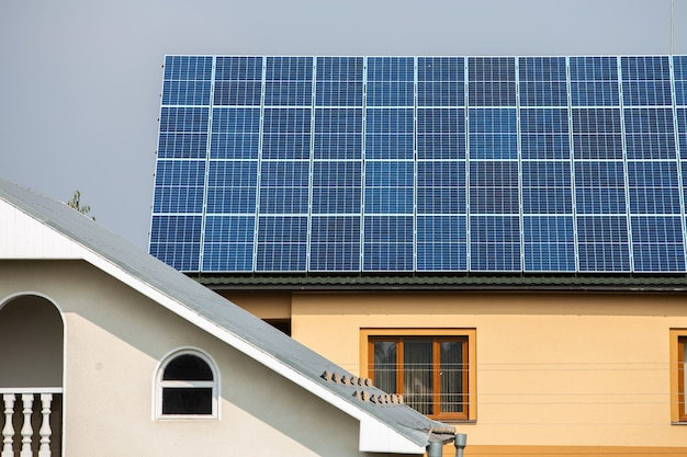 Fachada de uma casa particular com painéis solares foto voltaicos no telhado.
