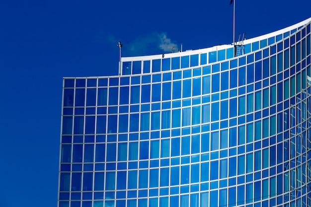 Fachada de vidro do edifício moderno, refletindo o céu azul