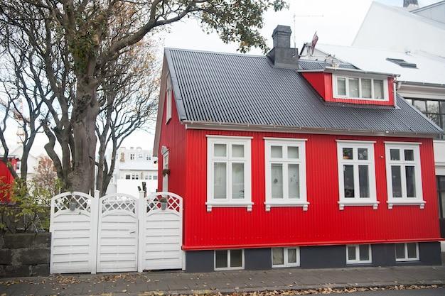 Fachada do edifício com parede vermelha e caixilharia branca. conceito de projeto de arquitetura. projeto da casa escandinava e estilo nórdico. casa vermelha elegante. casa brilhante no dia nublado de rua escandinava usual.