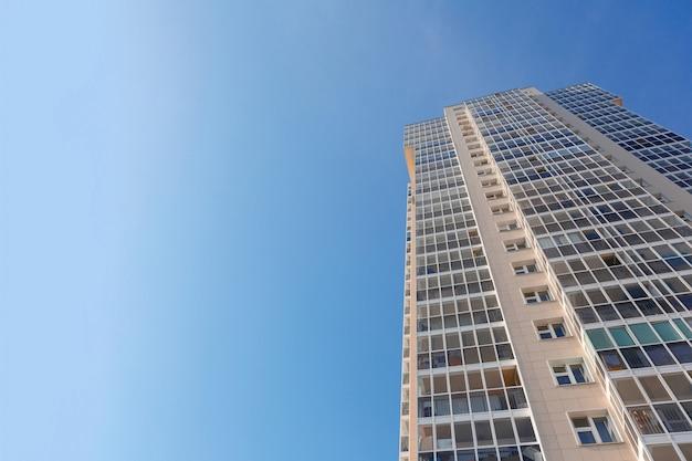 Fachada do novo prédio alto contra o céu azul, vista de baixo indústria da construção civil