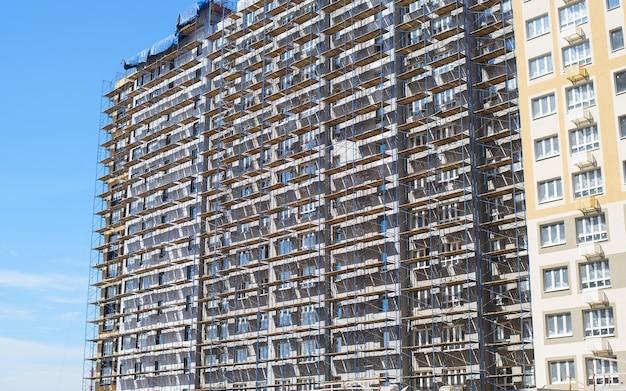 Fachada exterior de edifício de vários pisos em construção. prédio de apartamentos alto e andaimes. local de construção.