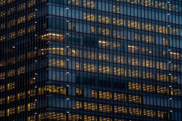 Fachada externa de vidro com iluminação interna amarela brilhando em cada andar em um arranha-céu