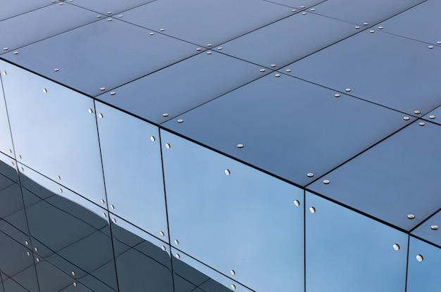 Fachada moderna do edifício com superfície de vidro, close-up vista diagonal.