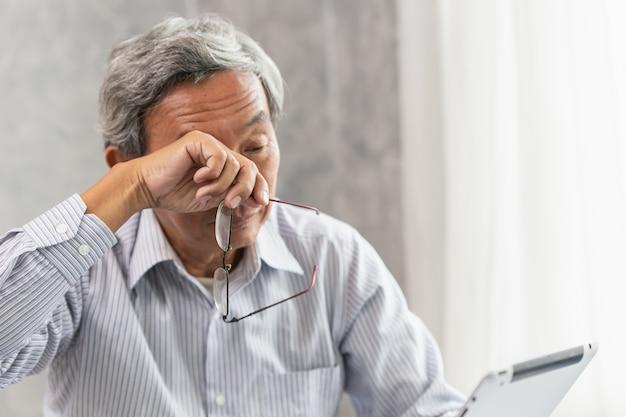 Fadiga de problema de irritação de olho idosos asiáticos e cansado de trabalho duro ou síndrome de visão de computador