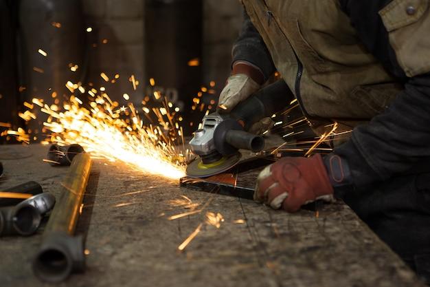 Faíscas brilhantes voam quando o trabalhador tritura a estrutura de metal.