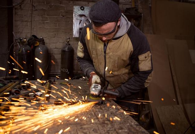 Faíscas brilhantes voam quando o trabalhador tritura a estrutura metálica.