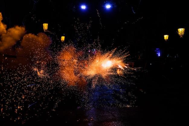Faíscas das cores na noite causada pelo fogo de um foguete, fundo preto.