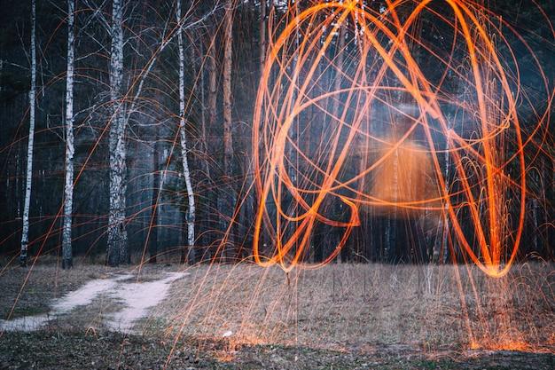 Faíscas de lã de aço na floresta à noite