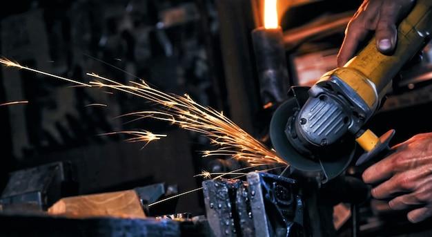 Faíscas feitas usando o moedor de disco elétrico que lustra a superfície de metal