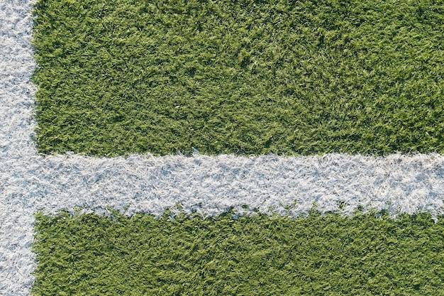 Faixa branca no campo para o futebol. textura verde de um campo de futebol, voleibol e basquete