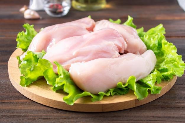 Faixa crua da galinha e salada verde em uma placa de corte redonda em um fundo de madeira da tabela.