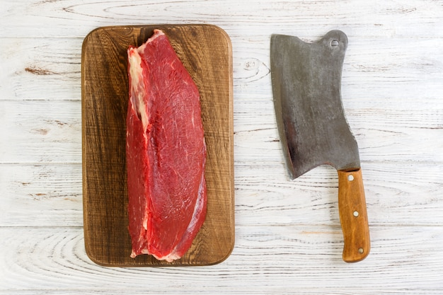 Faixa crua fresca vermelha da vitela da carne na placa de corte. fundo de madeira branco