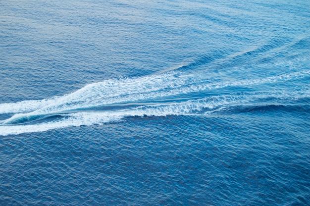 Faixa de barco no mar, espuma branca, ondas azuis, fundo bonito