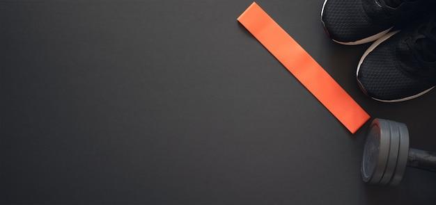 Faixa de borracha elástica vermelha, tênis e halteres em preto. postura plana