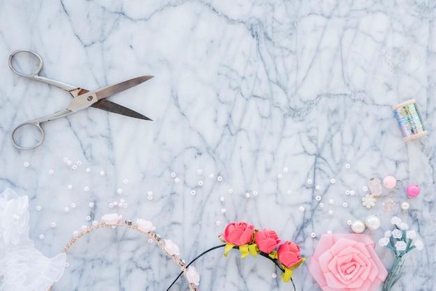 Faixa de cabelo artesanal com miçangas; flor rosa; carretel e tesoura em pano de fundo texturizado mármore