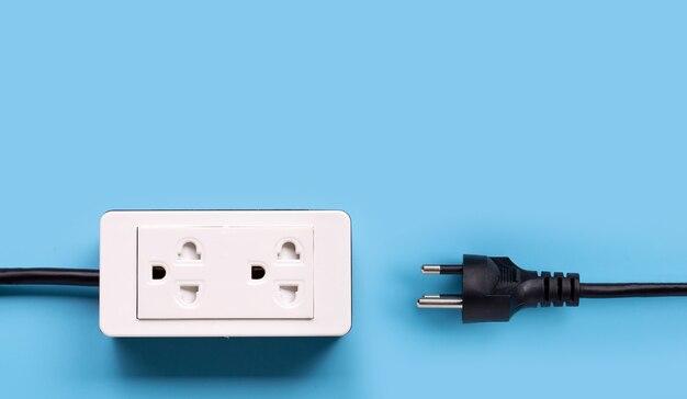 Faixa de energia elétrica e plugue na superfície azul
