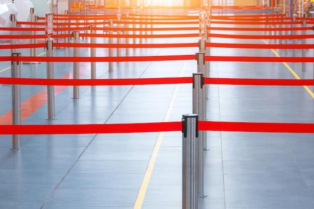Faixa de limite marcada com uma fita vermelha para uma linha de pessoas.