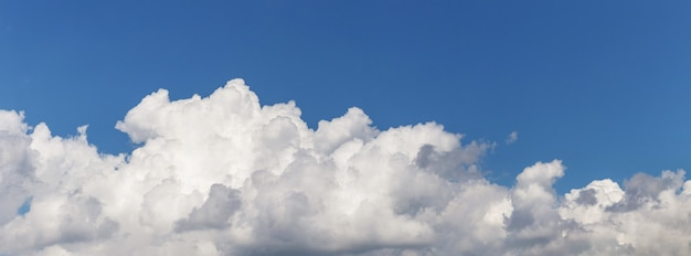 Faixa de nuvens brancas encaracoladas em um céu azul, panorama