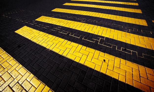 Faixa de pedestres amarela na estrada, fundo abstrato.