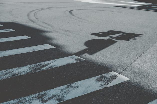 Faixa de pedestres ao lado da sombra da placa de rua