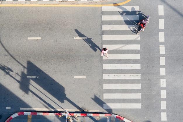 Faixa de pedestres de vista aérea superior com pessoas atravessar a estrada com sinalização. peões de conceito passando uma faixa de pedestres.