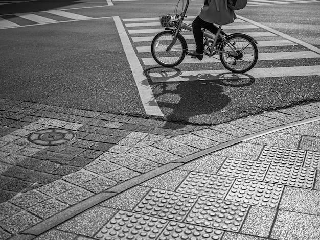 Faixa de pedestres, textura de rua de asfalto e mulher andando de bicicleta na cidade