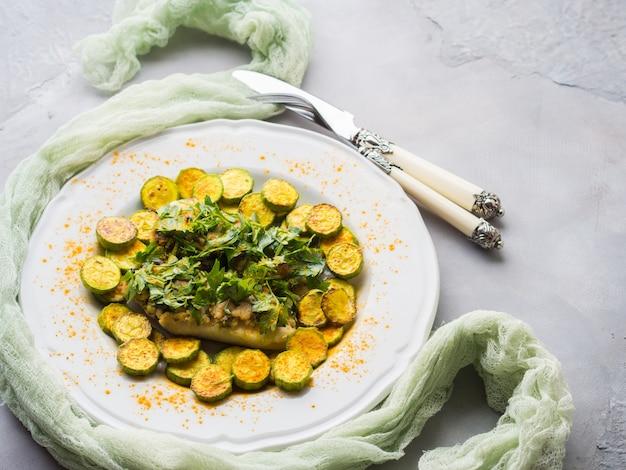 Faixa de peixes conservada em estoque cozida com courgettes da cobertura e da cúrcuma da salsa da amêndoa na placa branca. prato de dieta saudável