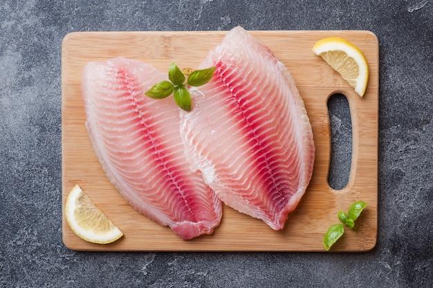Faixa de peixes crus do tilapia em uma placa de corte com limão e especiarias. mesa escura