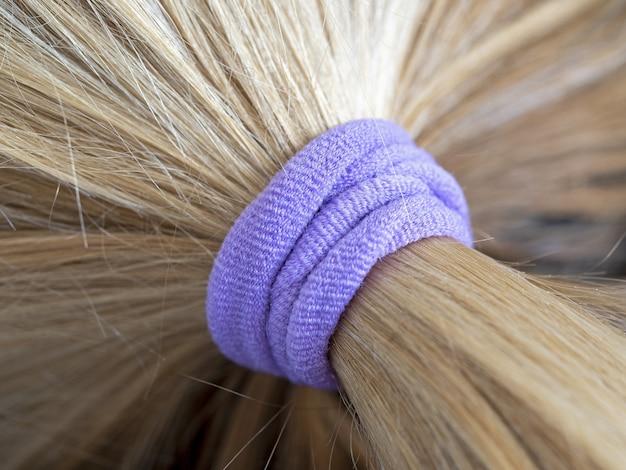 Faixa elástica roxa em seus cabelos loiros em um coque