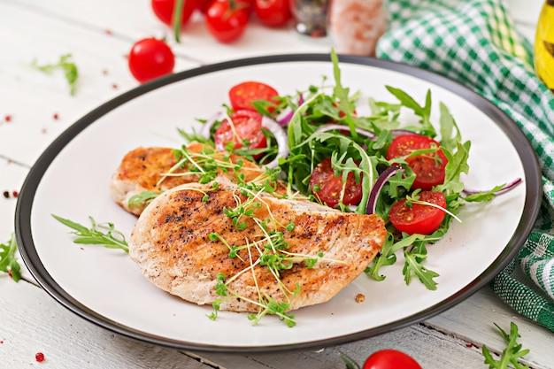 Faixa grelhada da galinha e salada do legume fresco dos tomates, da cebola vermelha e da rúcula.