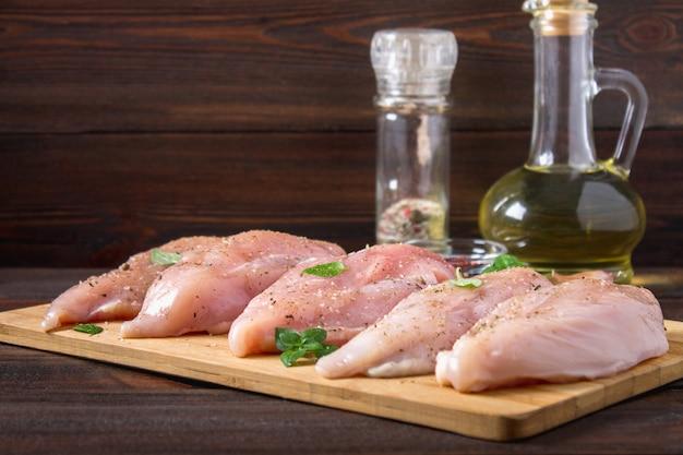 Faixas cruas da galinha em uma placa de corte na perspectiva de uma tabela de madeira.