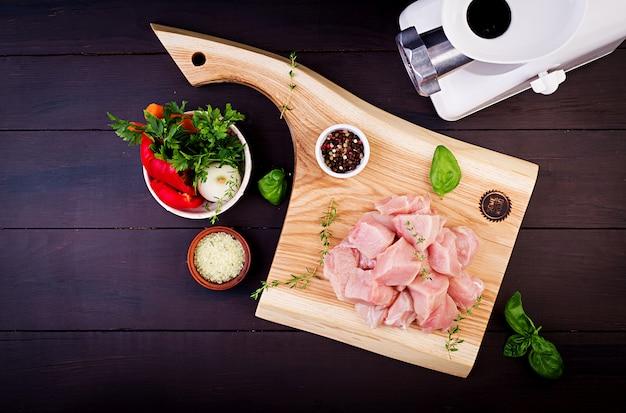 Faixas cruas do peito de frango na placa de corte de madeira com ervas e especiarias. vista do topo