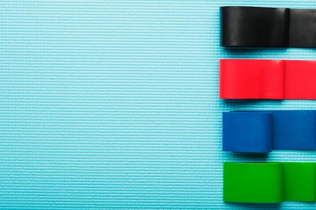 Faixas elásticas de fitness de diferentes cores e cargas para esportes