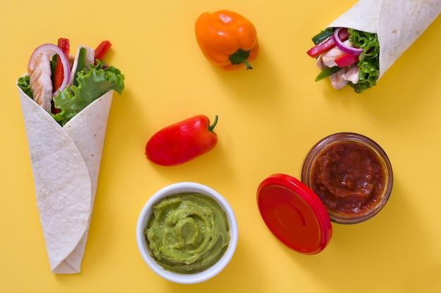 Fajita de frango mexicano com pimentão alface e cebola na mesa amarela