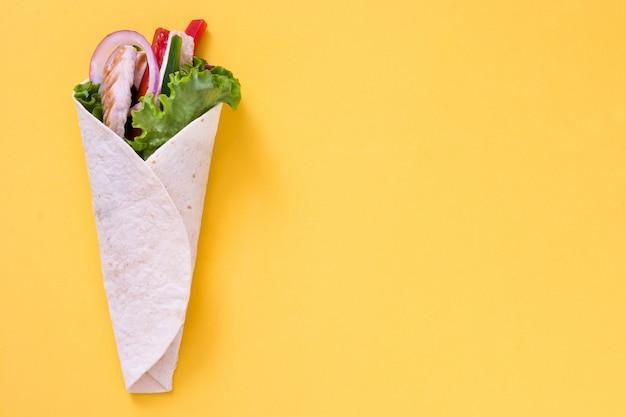 Fajita de frango mexicano com pimentão alface e cebola no espaço da cópia de mesa amarela