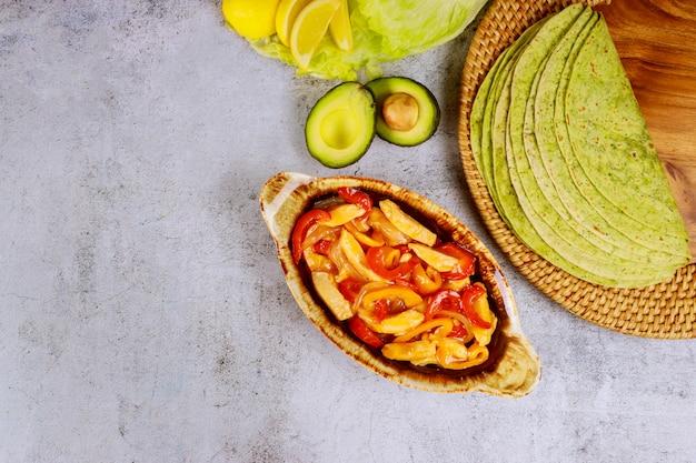 Fajita na assadeira com tortilhas de limão e espinafre na mesa branca