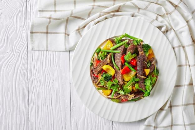 Fajitas de carne em um prato branco com brócolis, feijão verde, pimentão amarelo e vermelho, salsa, cebola em uma mesa de madeira branca com um pano de prato de cozinha, vista de cima, espaço de cópia