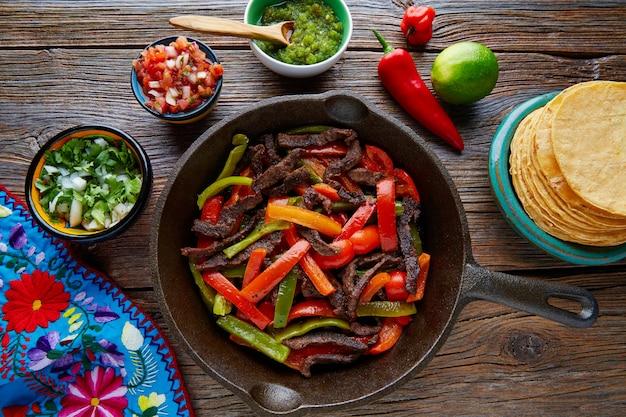 Fajitas de carne em uma panela com molhos comida mexicana