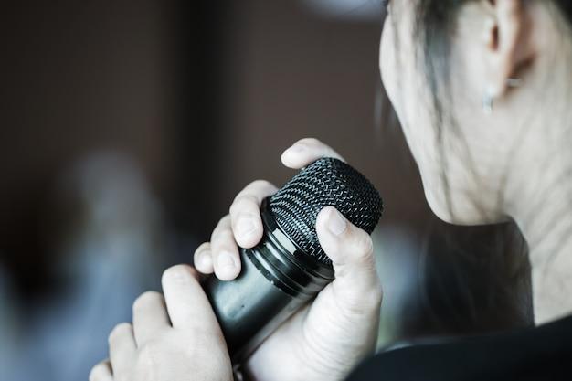 Fala de mulher de negócios inteligente e falando com microfone falando