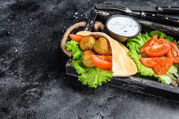 Falafel com legumes, molho em pão pita, sanduíche de kebab vegetariano. fundo preto. vista do topo. copie o espaço.